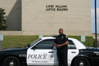 Public Information Officer Davis in front of patrol car